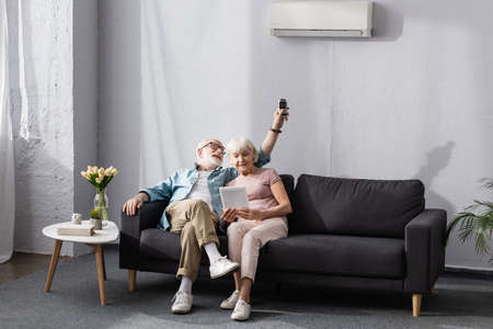 Senior woman using digital tablet near smiling husband switching air conditioner with remote controller