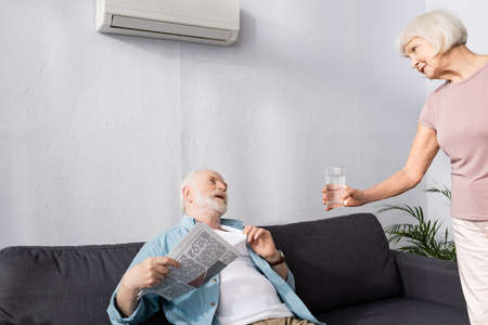 Elderly woman giving glass of water to husband holding newspaper under air conditioner at home