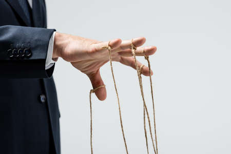 cropped view of puppeteer with strings on fingers isolated on gray Foto de archivo