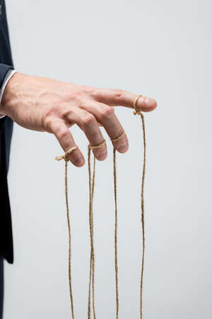 partial view of puppeteer with strings on fingers isolated on gray