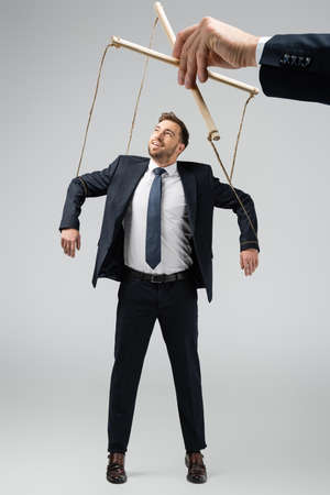 cropped view of puppeteer holding smiling businessman marionette on strings isolated on gray