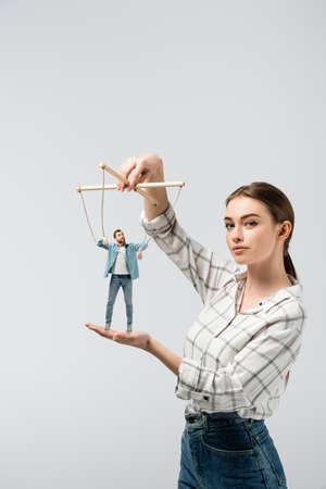 female puppeteer holding male marionette isolated on gray
