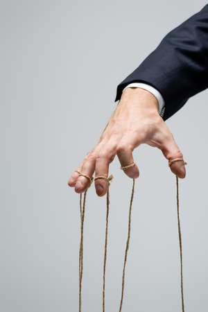cropped view of puppeteer with strings on fingers isolated on gray