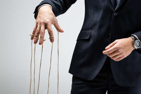 partial view of puppeteer in suit with strings on fingers isolated on gray