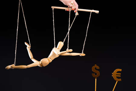 cropped view of puppeteer holding wooden marionette on strings near currency signs isolated on black