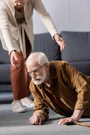 cropped view of woman helping fallen senior husband to get up from floor