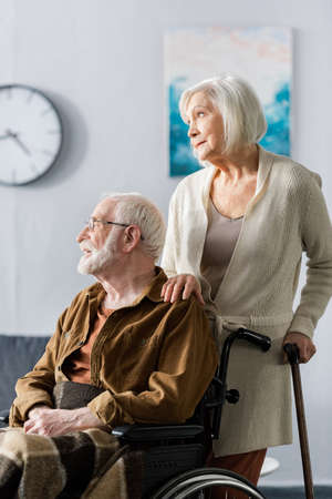 senior woman with walking stick touching shoulder of disabled husband sitting in wheelchair