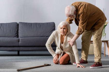 senior man helping wife sitting on floor near walking stick Reklamní fotografie