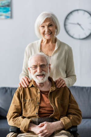 happy senior woman touching shoulders of smiling husband sitting in wheelchair Imagens