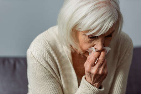 depressed senior woman crying while holding paper napkin Stock Photo