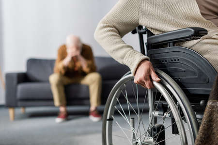 cropped view of disabled woman in wheelchair, and senior, despaired man sitting on sofa and obscuring face with hands