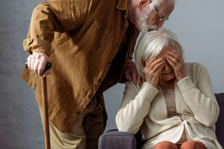 senior man with walking stick kissing head of diseased wife crying and covering eyes with hands