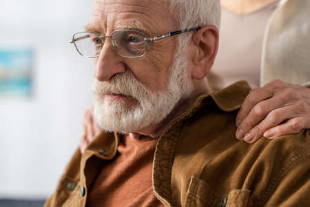 cropped view of woman touching shoulders of senior husband, sick on dementia Stockfoto