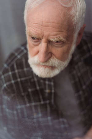 selective focus of depressed senior man looking away through window glass