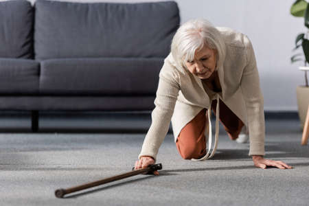 fallen, helpless senior woman trying to get walking stick on floor Zdjęcie Seryjne