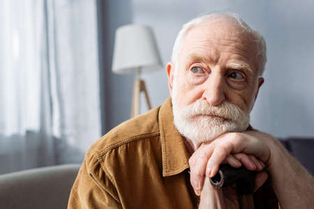 senior, lonely man looking away while sitting and leaning on walking stick Zdjęcie Seryjne