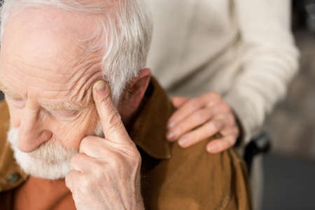 cropped view of woman touching shoulder of husband, sick on dementia, sitting with closed eyes and touching head Stockfoto