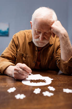 selective focus of senior man collecting jigsaw puzzle as dementia therapy Zdjęcie Seryjne