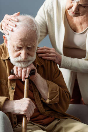 senior woman calming diseased old husband, sick on dementia, while touching his head and shoulder