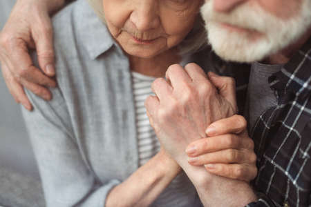 partial view of senior man and his wife, sick on dementia, holding hands while standing by window