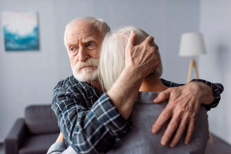senior, sad man hugging wife, sick on dementia, and looking away
