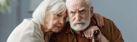 horizontal image of senior woman with closed eyes hugging husband, sick on dementia
