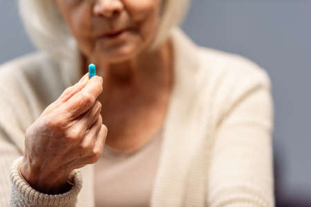 cropped view of senior woman holding pill, selective focus