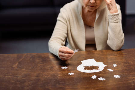senior woman collecting jigsaw puzzle as dementia therapy
