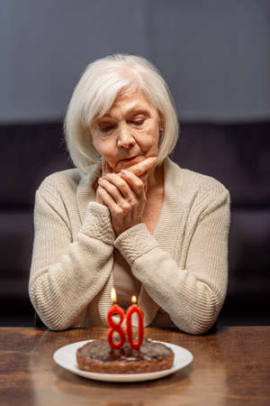 lonely senior woman looking at birthday cake with number eighty and burning candles