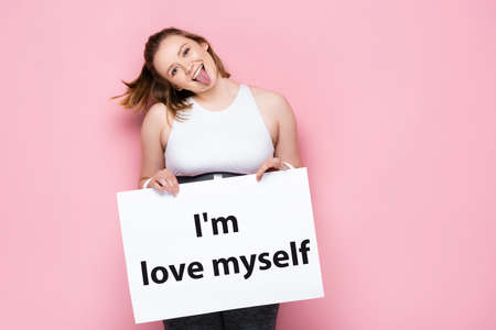 cheerful overweight girl holding placard with i love myself inscription and sticking out tongue on pink