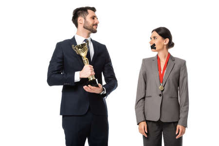 businessman holding golden trophy and looking at businesswoman with duct tape on mouth isolated on white Standard-Bild