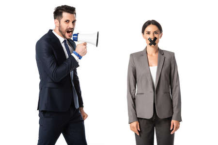 bearded businessman screaming in megaphone near businesswoman with duct tape on mouth isolated on white, gender inequality concept Standard-Bild