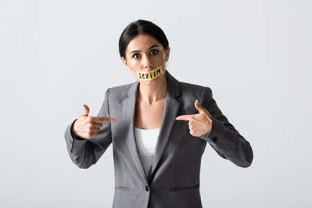 Businesswoman with sexism lettering on duct tape looking at camera while pointing with fingers at herself isolated on white