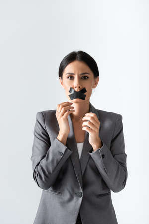businesswoman with duct tape on mouth looking at camera isolated on white, gender inequality concept