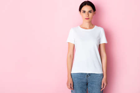 beautiful woman in white t-shirt looking at camera on pink