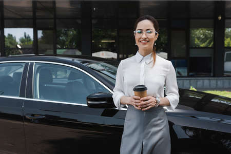 Beautiful businesswoman smiling at camera while holding paper cup near auto on urban street