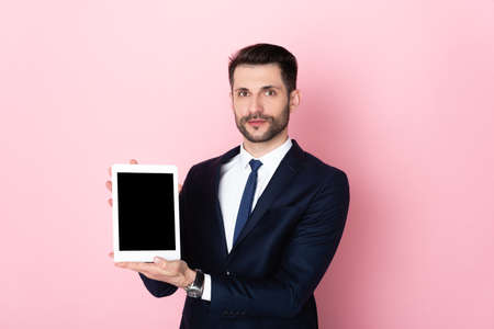 handsome businessman holding digital tablet with blank screen on pink