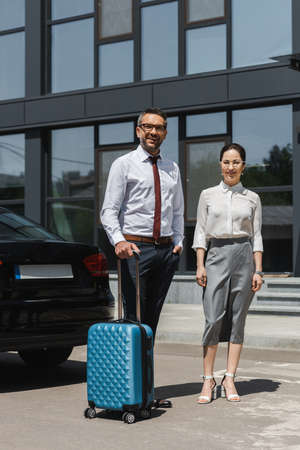 Smiling businessman holding suitcase near businesswoman and car on urban street