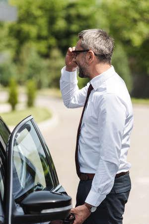 Side view of positive businessman adjusting eyeglasses and opening door of car on urban street