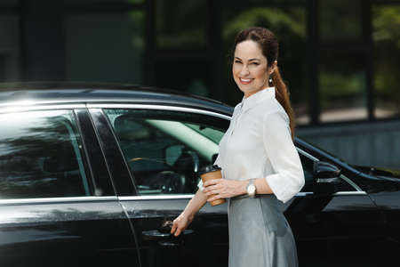Side view of beautiful businesswoman smiling at camera while holding paper cup and opening car door on urban street