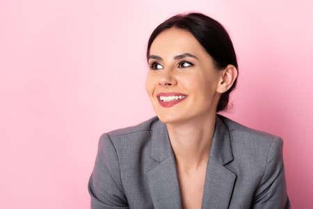 happy businesswoman in suit looking away on pink