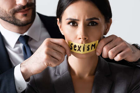 bearded businessman touching duct tape with sexism lettering on mouth of businesswoman looking at camera isolated on white