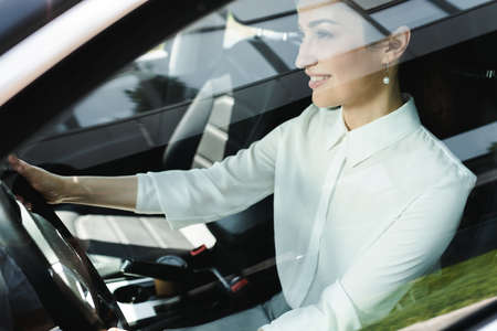 Selective focus of smiling businesswoman driving car Reklamní fotografie