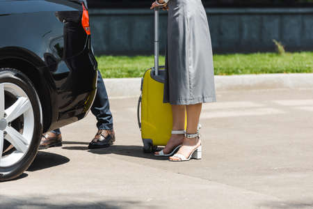 Cropped view of businesswoman with suitcase standing near businessman and car on urban street Reklamní fotografie