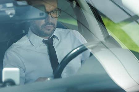 Selective focus of businessman in formal wear driving car Reklamní fotografie