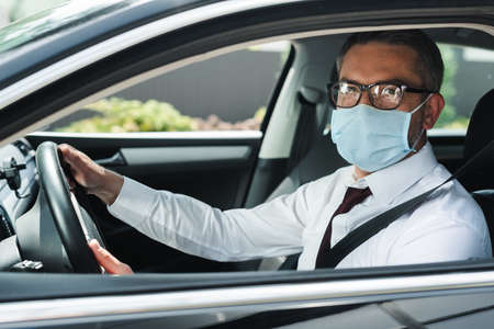 Selective focus of businessman in eyeglasses and medical mask looking at camera while driving car