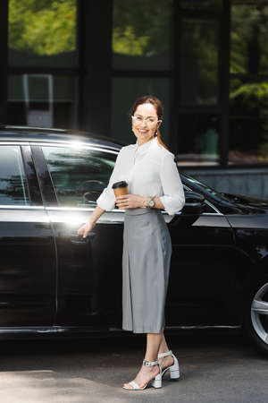 Smiling businesswoman holding paper cup and opening car door on urban street Reklamní fotografie
