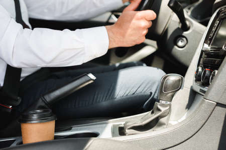Cropped view of businessman in formal wear driving car near paper cup in cup holder at daylight
