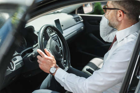 Selective focus of businessman sitting on driver seat in car with open door