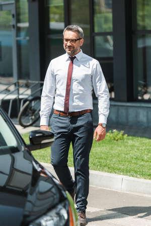Selective focus of handsome businessman walking to car on urban street Reklamní fotografie